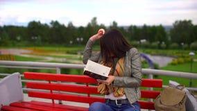 有镜片的年轻美丽的妇女读书的坐一条长凳外面在一个公园在夏天 吃苹果计算机的她 股票录像