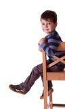 有镶边T恤杉的微笑的男孩坐在白色ba的一把凳子 库存照片