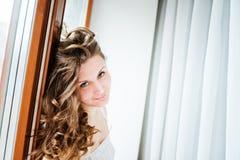 有长卷曲的美丽的年轻愉快的微笑的妇女 免版税库存照片