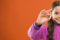 有长发举行药片手指的女孩 维生素概念 需要维生素补充 怎么适当作为维生素 作为 免版税库存照片