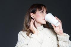 有长发佩带的毛线衣的美女拿着纸一次性咖啡杯 与轻松的外形面孔的饮用的咖啡 免版税库存图片