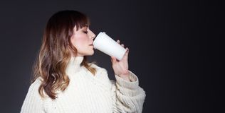 有长发佩带的毛线衣的美女拿着纸一次性咖啡杯 与轻松的外形面孔的饮用的咖啡 免版税库存照片