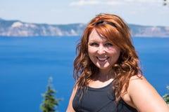 有长发姿势的红发女性在明亮的蓝色湖-火山口湖前面 免版税库存图片