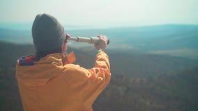 有长发的一个女孩在一个救生服和一个灰色盖帽在山站立并且通过望远镜看 股票视频