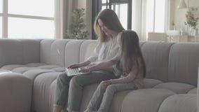 有长发的一起坐沙发在客厅键入在膝上型计算机的一个年轻母亲和小女儿 影视素材