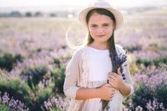 有长发的俏丽的女孩在一件亚麻制礼服和一个帽子有站立在淡紫色领域的淡紫色花束的 免版税库存照片