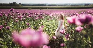 有长发的可爱的女孩在白色礼服偏僻走在淡紫色鸦片花田 免版税库存照片