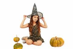 有长发的女孩在巫婆成套装备在万圣节用南瓜,情感地仿造物表示  图库摄影