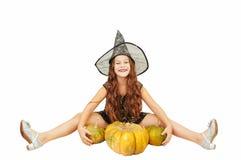 有长发的女孩在巫婆成套装备在万圣节用南瓜,情感地仿造物表示  免版税库存照片