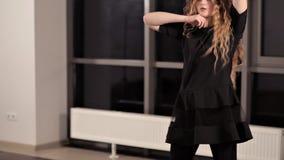 有长发的少女在一套黑衣服火车在大厅里,精力充沛的跳舞 股票视频
