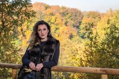 有长发的年轻美女,在毛皮夹克,在木栏杆站立在一明亮的好日子,当走在秋天时 免版税图库摄影