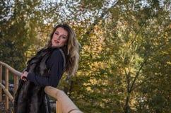 有长发的年轻美女,在毛皮夹克,在木栏杆站立在一明亮的好日子,当走在秋天时 库存照片