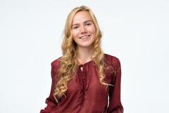 有长发的微笑愉快的白肤金发的女孩在红色衬衣看照相机 库存照片