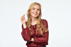 有长发的微笑愉快的白肤金发的女孩在红色衬衣看照相机 免版税图库摄影