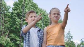 有长发的指向去举行的手的画象可爱的男孩和美女在摇摆附近,愉快地微笑 A 影视素材