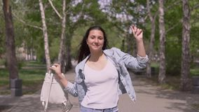 有长发的滑稽的女孩有在她的手步行的一个背包的在晴朗的滑稽天气和的舞蹈的街道下 ? 影视素材