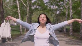 有长发的滑稽的女孩有在她的手步行的一个背包的在滑稽的街道和的舞蹈下 t 影视素材