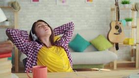 有长发的美丽的亚裔女孩在一个现代房子的客厅有耳机的听音乐和放松的 影视素材