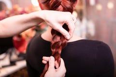 有长发的美丽,红发女孩,美发师编织法国辫子,在发廊 专业护发 库存照片
