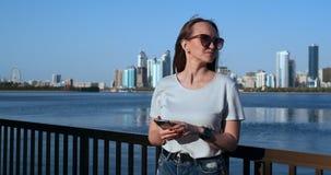 有长发的美女在使用智能手机应用程序的太阳镜在日落在4K附近的河码头 股票视频