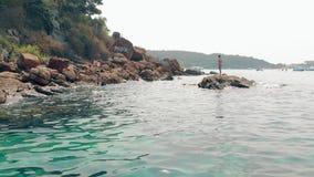 有长发的被晒黑的夫人在石头的红色泳装立场 影视素材