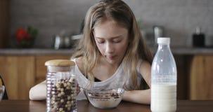 有长发的逗人喜爱的女孩以胃口吃着巧克力玉米片用牛奶 影视素材