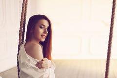 有长发的逗人喜爱的年轻红头发人妇女坐在人的衬衣的摇摆 免版税库存照片
