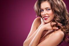 有长和发光的波浪发的性感的女孩 美好的模型,在红色背景的卷曲发型 免版税库存图片