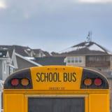 有长方形窗口和几尽管信号灯的正方形黄色学校班车在后方 免版税库存图片
