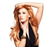有长期平直的红色头发的美丽的妇女在一件黑礼服。 免版税库存照片