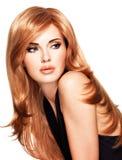 有长期平直的红色头发的美丽的妇女在一件黑礼服。 免版税库存图片