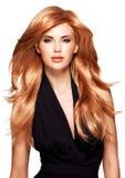 有长期平直的红色头发的美丽的妇女在一件黑礼服 库存照片