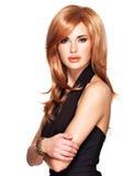 有长期平直的红色头发的美丽的妇女在一件黑礼服 免版税库存照片
