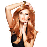 有长期平直的红色头发的美丽的妇女在一件黑礼服 图库摄影