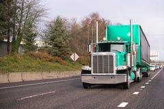 有长期被盖的半拖车的绿色经典大半船具卡车 图库摄影