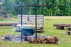 有长木凳的营火站点在乡间别墅附近 库存图片