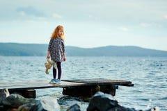 有长毛绒兔宝宝的一个孤独的女孩在码头和厕所站立 免版税库存图片