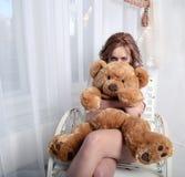 有长毛绒熊的恼怒的女孩坐椅子在窗口附近 免版税库存图片