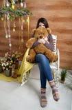有长毛绒熊的恼怒的女孩坐椅子 免版税库存图片
