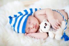 有长毛绒玩具的休眠的男婴 库存图片