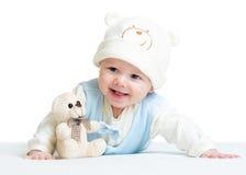 有长毛绒玩具的微笑的婴孩weared帽子 库存图片