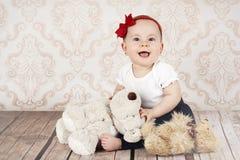 有长毛绒玩具的笑的小女婴 免版税图库摄影