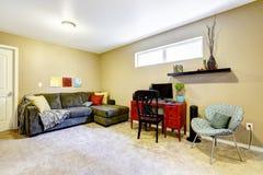 有长沙发和书桌的地下室室 免版税库存照片