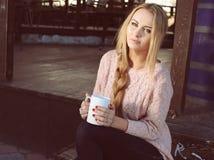 有长白肤金发的妇女穿偶然舒适衣裳喝茶的 图库摄影