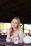 有长白肤金发的妇女穿偶然舒适衣裳喝茶的 库存照片