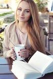 有长白肤金发的妇女穿偶然舒适衣裳喝茶的 免版税库存照片