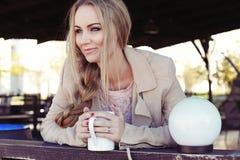 有长白肤金发的妇女穿偶然舒适衣裳喝茶的 免版税库存图片