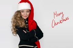 有长白肤金发的惊人的美丽的小女孩,穿戴在一个红色盖帽圣诞老人和典雅的衣裳 免版税图库摄影