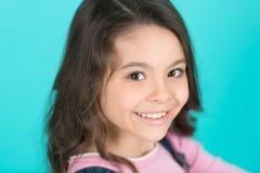 有长的健康深色的头发的愉快的女孩在蓝色背景 有微笑的孩子在可爱的面孔 擦亮沙龙的秀丽nailfile钉子 Skincare 库存照片
