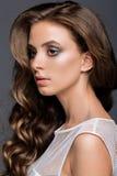 有长的光滑的卷曲发型的少妇 免版税库存照片